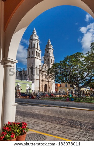 Towers of Campeche cathedral as seen from across the square under an arched colonnade - stock photo