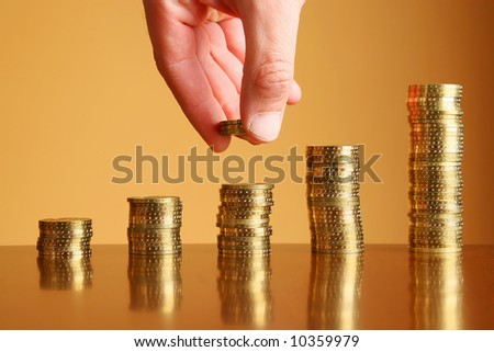 towers of gold coins on the table and hand - stock photo