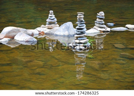 Towers of small pebbles in the middle of a shallow river - stock photo