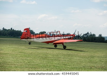 Towing red aircraft on a grassy airport ready for takeoff. - stock photo
