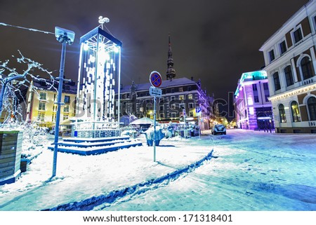 Town hall in Old Riga, Latvia at winter night with Saint Peter's church  - stock photo