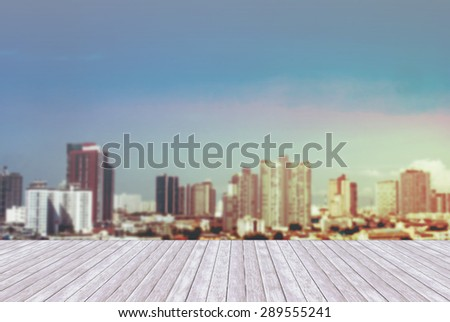 town of blurred blue color and wooden terrace space front at sunset