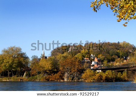 Town of Harpers Ferry National Historical Park in West Virginia as seen from Maryland looking across the Potomac River in autumn. - stock photo
