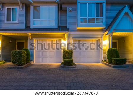 Townhouses, homes, community, garages at  dusk, night time in suburbs of Vancouver, Canada. - stock photo
