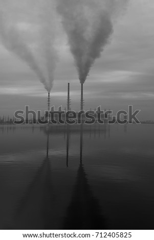 toxic effects of plants and factories, their exhaustion of fumes into the air, nearby lake and reflection of of the pipes in the water