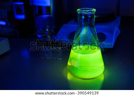 Toxic green liquid in measure flask in chemical laboratory under UV light  - stock photo