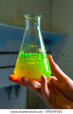 Toxic green liquid in messure flask in chemical laboratory  - stock photo