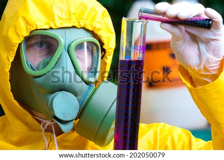 Toxic substances ; Chemist with the gas mask and the protective suit examining toxic supsance ,photography - stock photo