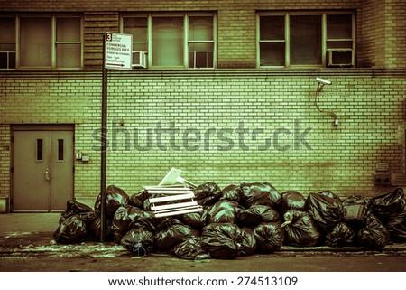 Toxic toned image of pile of plastic trash bags on urban street - stock photo