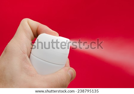 Toxic vapor being sprayed from a white can by a man's hand over an important alerted dangerous red background suggesting unhealthy gas and ozone layer problems in a close view - stock photo