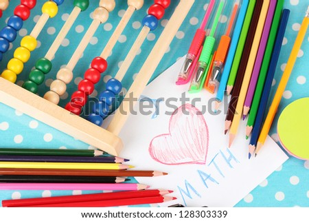 Toy abacus, note paper, pencils on bright background