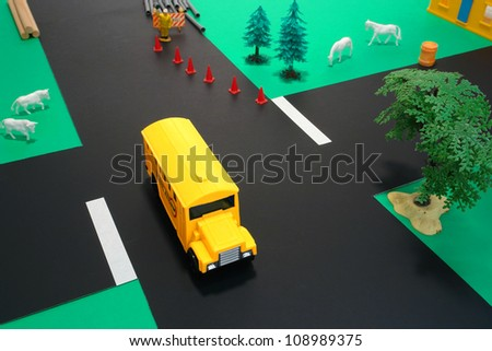 Toy American yellow school bus in driver safety education diorama driving at dangerous road intersection with various safety hazard and danger such as construction and livestock or trees and obstacles - stock photo