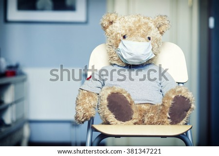 Toy bear in medical bandage on face sitting on the chair - stock photo