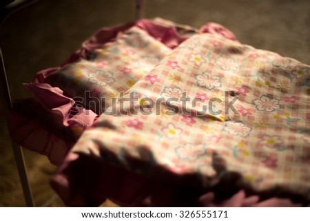 Toy bed in morning light with pillow and quilt cover with pink flower ornament, close-up - stock photo