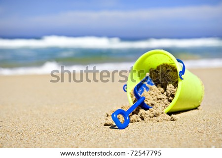 Toy bucket and shovel on the beach - stock photo