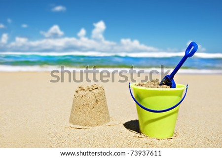 Toy bucket and shovel on the beach on a sunny day - focus on the shovel handle - stock photo