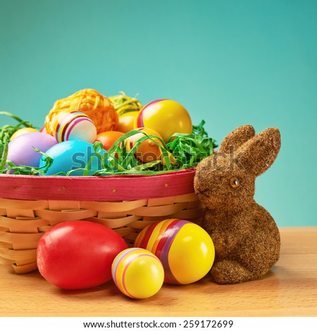 Toy bunny and basket full of colorful Easter eggs as a festive background composition - stock photo