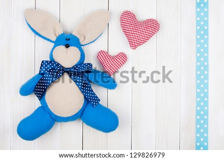 Toy bunny, love hearts on wood background - stock photo