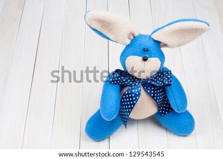 Toy bunny on white wood background - stock photo