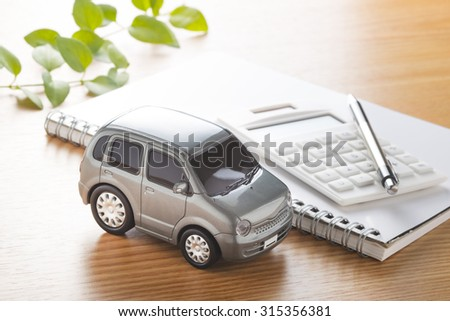Toy car and calculator on the table.,to buy,sell,rent,repair or insurance  - stock photo