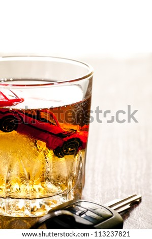 Toy car in a glass of whisky close up with a don't drink and drive concept - stock photo
