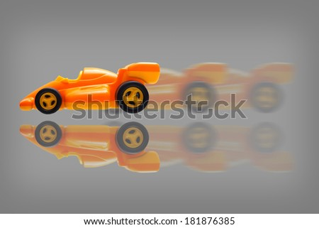 Toy car in motion over gray background - stock photo