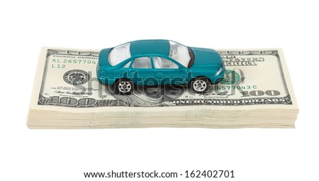 Toy car on the stack of dollar bills isolated on white background - stock photo