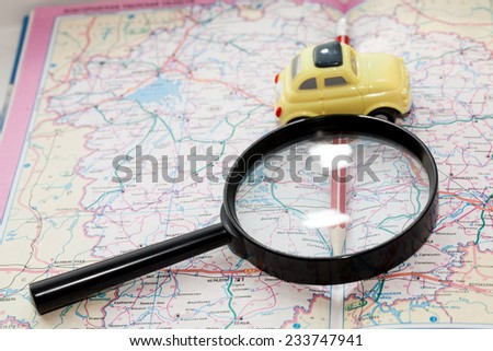 Toy car, pencil and magnifying glass on a road atlas