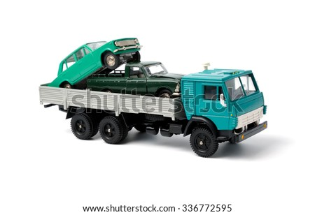 Toy cars in the back of toy truck on a white background - stock photo