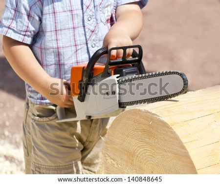 toy chainsaw in the hands of the child - stock photo