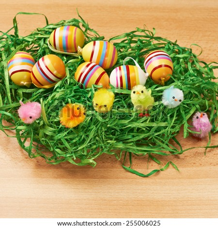 Toy chickens and Easter eggs over the pile of green ribbons as artificial grass - stock photo