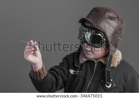 toy, child playing the aircraft pilot with hat and retro bomber jacket - stock photo