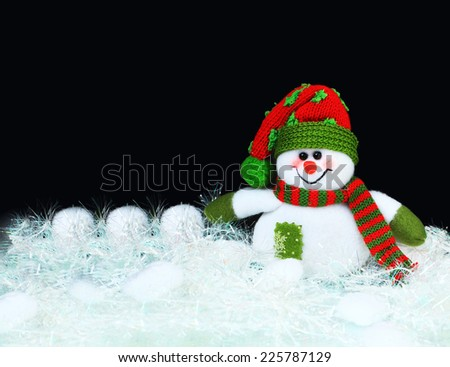 Toy decorated with a snowman, on a black background - stock photo