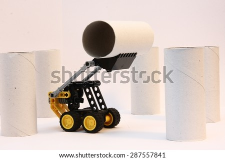 toy digger lifts paper tube - stock photo