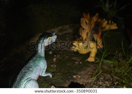 Toy dinosaur figurine in a real nature scenery outdoors. Two dinosaurs fighting