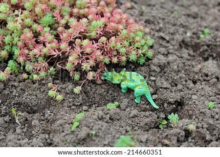 Toy dinosaur near plants - stock photo