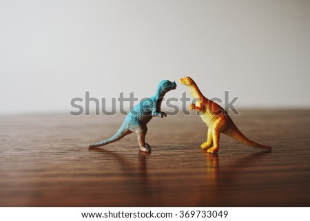 Toy dinosaurs on a table. - stock photo
