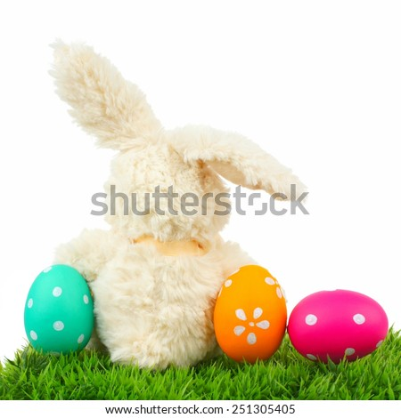 Toy Easter bunny on grass with colorful eggs over a white background, behind view - stock photo