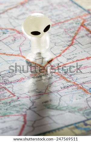 toy ET standing on a Map of New Mexico right above the city of Roswell - stock photo