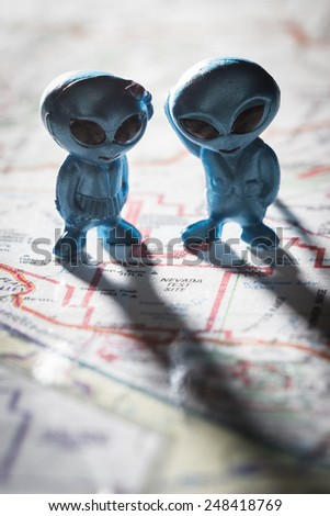 toy ETs standing on a Map of the United States, with the words Nevada test Site on the map - stock photo