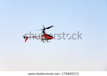 toy helicopter flying on blue sky background - stock photo