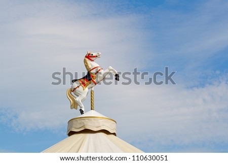 Toy horse atop a fairground roundabout - stock photo