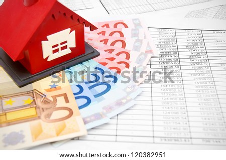 Toy house and money on the documents. - stock photo