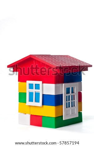 Toy house build with colorful plastic blocks isolated on white - stock photo