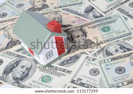toy house for dollar banknotes as background - stock photo