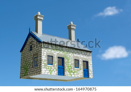 Toy house hover in the air aginst blue sky . Concept photo of Real estate market bubble , booming, money,price, rent, grid, home, house, housing, industry and subprime mortgage crisis. (Copy Space).