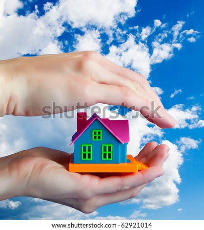 toy house in human hands - a symbol of protection ... Against the sky with clouds ... - stock photo
