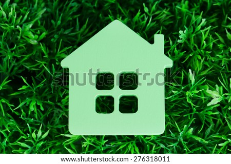 Toy house on grass close-up - stock photo