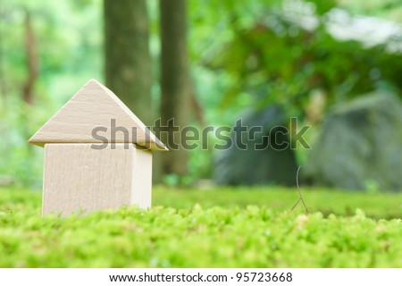 toy house on moss - stock photo