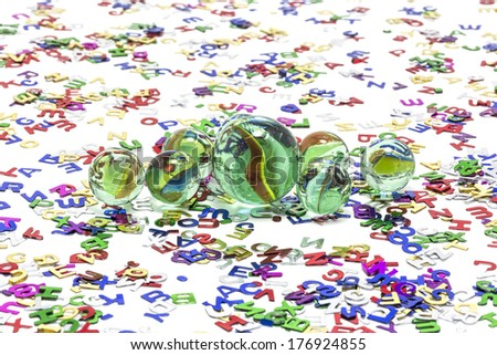 Toy marbles on white background, surrounded by so many multicolor letters. - stock photo